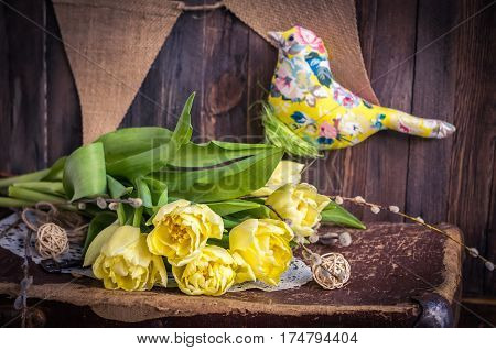 The daylight yellow tulips and the fabric bird composition on the wooden background. Horizontal studio shot. Spring still life
