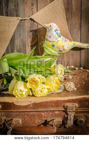 The daylight yellow tulips and the fabric bird composition on the wooden background. Vertical studio shot. Spring still life