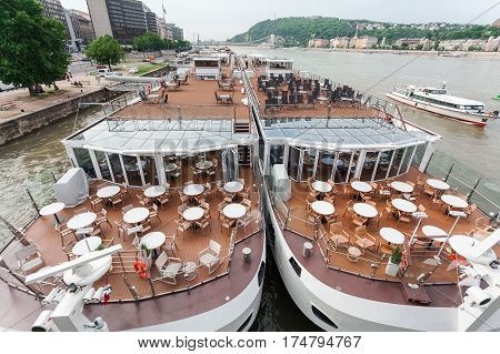 Moored on the banks of the river tourist boats on the deck with tables, Budapest, Hungary