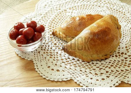 Russian pirozhki, baked patties or pies on basket with cherry