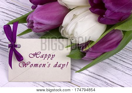 Purple And White Tulips With White Paper On A White Wooden Background And Card Lettering Happy Women