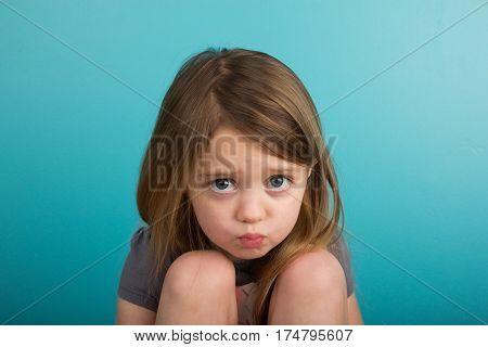 Little girl pouting against plain teal background