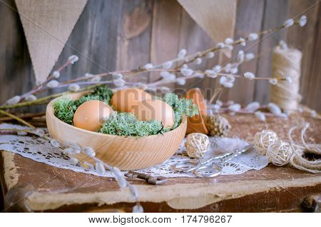 The Easter composition with eggs in wooden bowl and willow branches on a table in daylight.