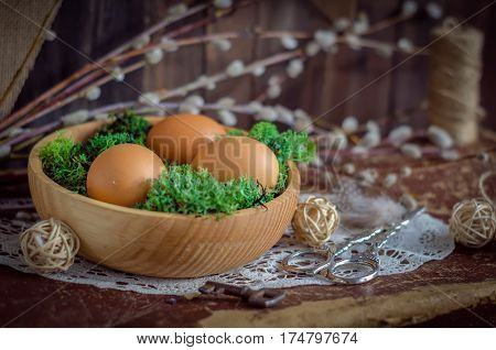 The Easter spring composition with eggs in wooden bowl and willow branches on a table in daylight.