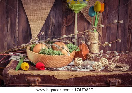 The Easter composition with eggs in a wooden bowl and textile bird in daylight. Spring morning still life