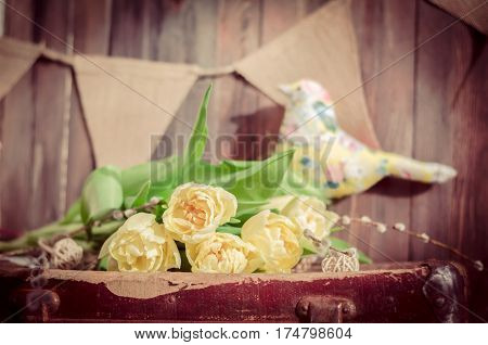 The yellow flowers on the background of a textile bird. Horizontal indoors shot.