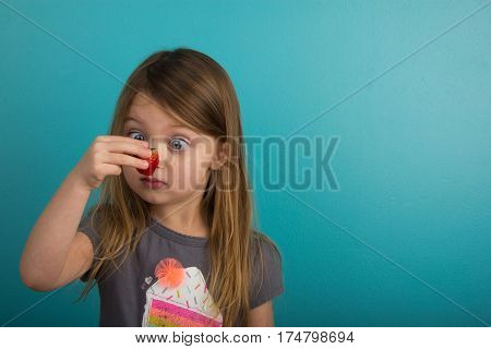 Little girl looking at a strawberry with big eyes