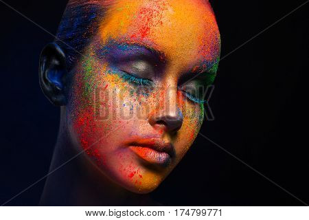 Creative art make up. Closeup cropped studio portrait of young fashion model with closed eyes and bright colorful mix of paint on her face. Color fantasy, artistic makeup.