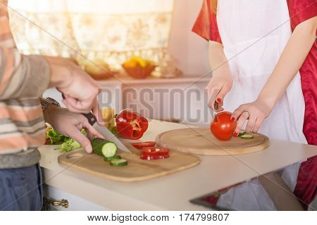 Hands of Wife and Husband cooking Salad together cutting Vegetables with Knife on cutting Board using Tomato red Pepper Carrot Cucumber and Cheese