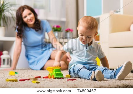 Mother with child playing in the home room