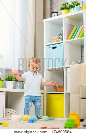 little baby boy at home in a room in the interior scattered toys