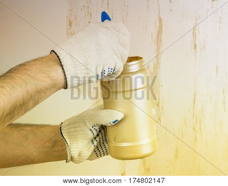 Male hand applied decorative paint on the wall with sand. Home repair concept.