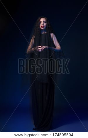 Young gothic female dressed in black looking away.