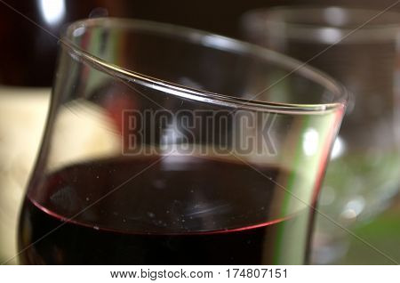 Half full glass of fresh delicious red wine, bottles in the background, Novi Sad, Serbia