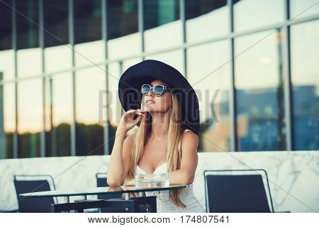 Young pretty sexy girl in hat sitting outdoor in cafe