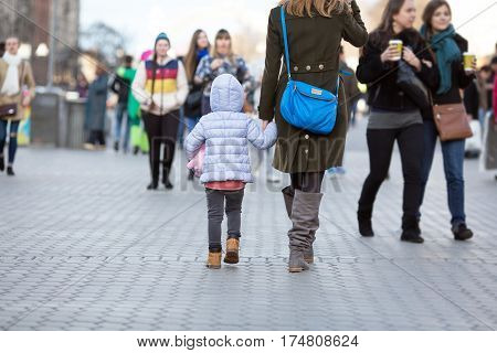 Elegant Lady and little Baby Girl walking on City Street among Crowd of People on Central Promenade on Weekend Springtime clothing Jacket and Coat Tenderness and Love concept.