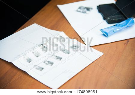 The investigation of the crime. The inspector takes fingerprints of a suspect