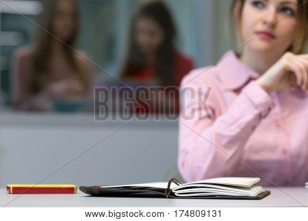 Young female Business Trainee working on Laptop Computer at grey Desk pensively looking aside thinking about new Idea - focus on Notepad face is blurred