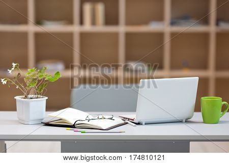 Cozy working Place on Wood Wall background - grey Table with Computer paper Workbook Flower green Coffee Mug and Glasses and wooden Cupboard with Shelves on blurred Background.