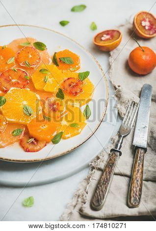 Fresh mixed citrus fruit salad with mint and honey on white ceramic plate over grey background, selective focus. Vegan, vegetarian, healthy, dieting, detox food, clean eating concept