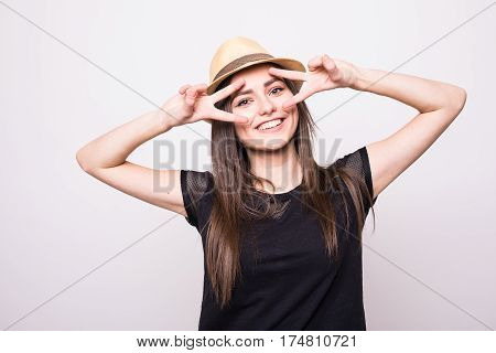 Cheerful girl in cap making faces on camera on grey back