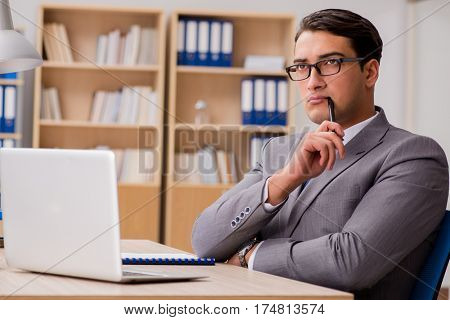 Young handsome businessman working on office