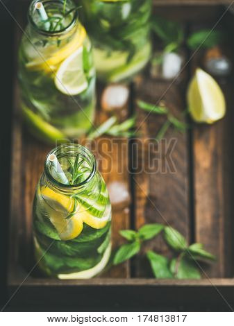 Citrus fruit and herbs infused sassi water for detox, healthy eating, dieting in glass bottles in wooden tray, selective focus, copy space. Clean eating, healthy lifestyle concept