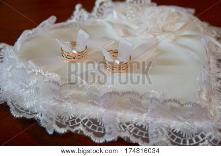 The gold wedding rings on the pincushion