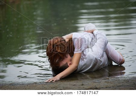 couple making love on the shore. Clothes are wet and the woman is laying on top of the man.
