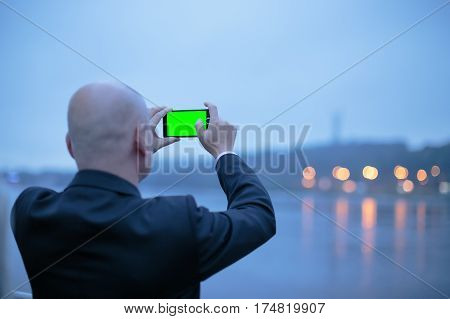 Man taking photo of beautiful evening landscape with mobile phoneMiddle age male tourist making mobile photo Back view of a bald businessman who taking a photo of coast landscape with smartphone.