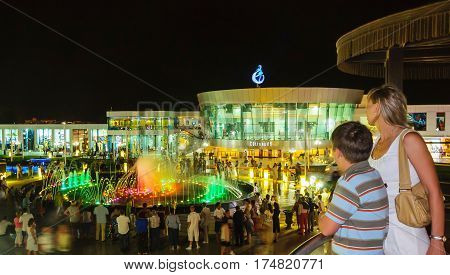 SHARM EL SHEIKH, EGYPT - MAY 24, 2010: People look at the beautiful light and music show. Colorful fountain in night at Soho square - cultural and entertainment center of Sharm El Sheikh
