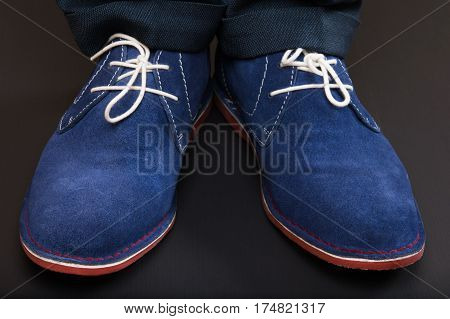 pair of male legs in blue shoes on black floor
