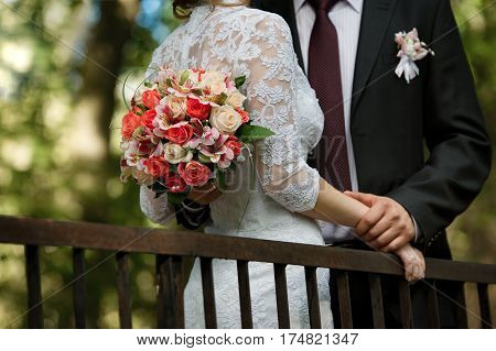 Wedding bouquet in hands of groom in wedding day. Bridal couple hugging