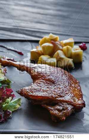 Roasted duck leg closeup, served on slate plate with lettuce. Restaurant food on black wood table, vertical