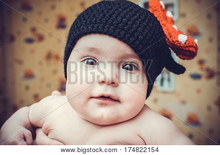 Little cute girl in black knitted hat looks at the world with their curious eyes.