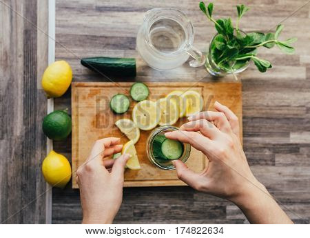 Women's hands preparing detox water with lemon, lime, mint and cucumber. Ingredients for infused water on a wooden board. Top view. Detox, diet concept. Healthy drink