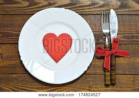 Valentines Day table setting: Plate and silverware on wooden table