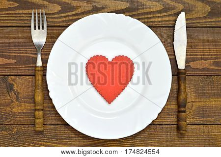 Plate decorated with red heart shaped ornament and silverware on wooden background