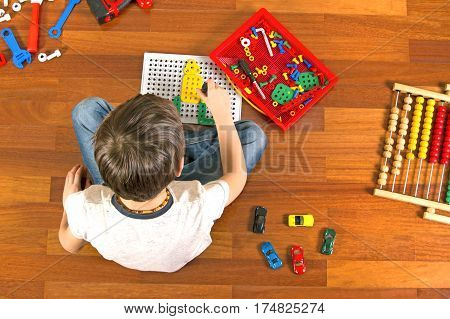 Little kid playing with toys tool kit while sitting on the floor in his room. Top view