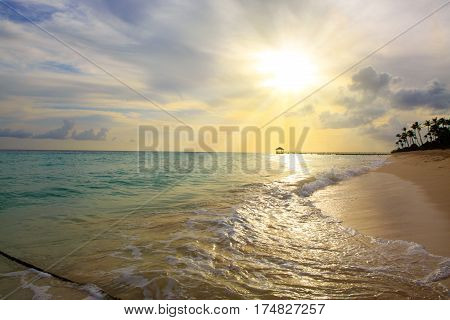 Beautiful Caribbean sea and palm trees. Golden sunrise sunset over the sea ocean.Beach of caribbean sea and wooden pier .