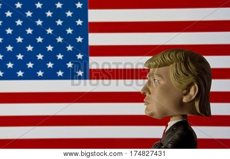 President Donald Trump Bobble head caricature figure standing in front of an American Flag