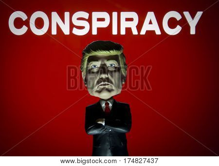 President Donald Trump Bobble head caricature figure standing in front of a sign reading Conspiracy