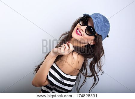Enjoyment Young Woman In Sunglasses And Blue Baseball Cap Posing And Looking With Happy Smile In Str