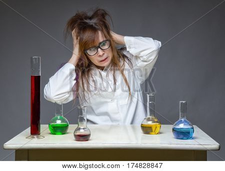 Grabbing head messy scientist in lab on gray background