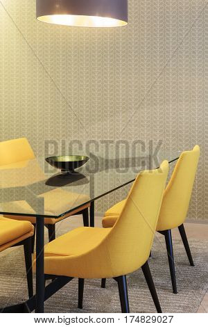 Yellow chairs with glass table in dinning room