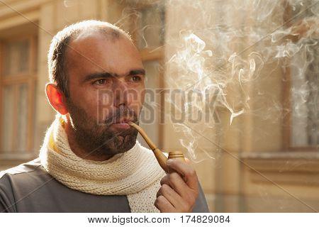 young businessman enjoying pipe smoking (tobacco smoke addiction)