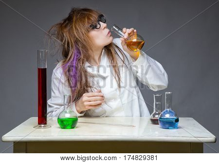 Drinking shaggy scientist in lab on gray background