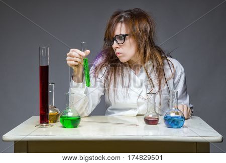 Skeptical shaggy scientist in lab on gray background