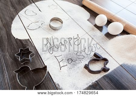 Symbolic image Easter cake with utensils on a dark wooden background. Rolling pin, cookie cutters cutting, eggs, flour