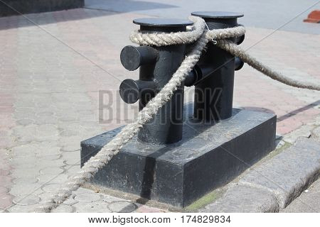 Marine bitt with a rope in a fence